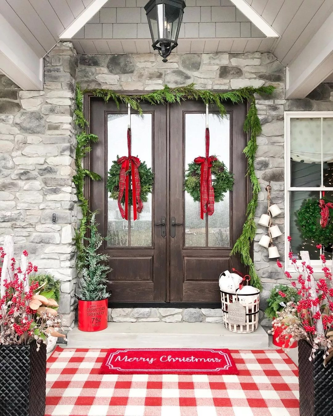Double front doors lined with garland and two wreathes hanging on the door windows. Photo by Instagram user @beyond_gray.