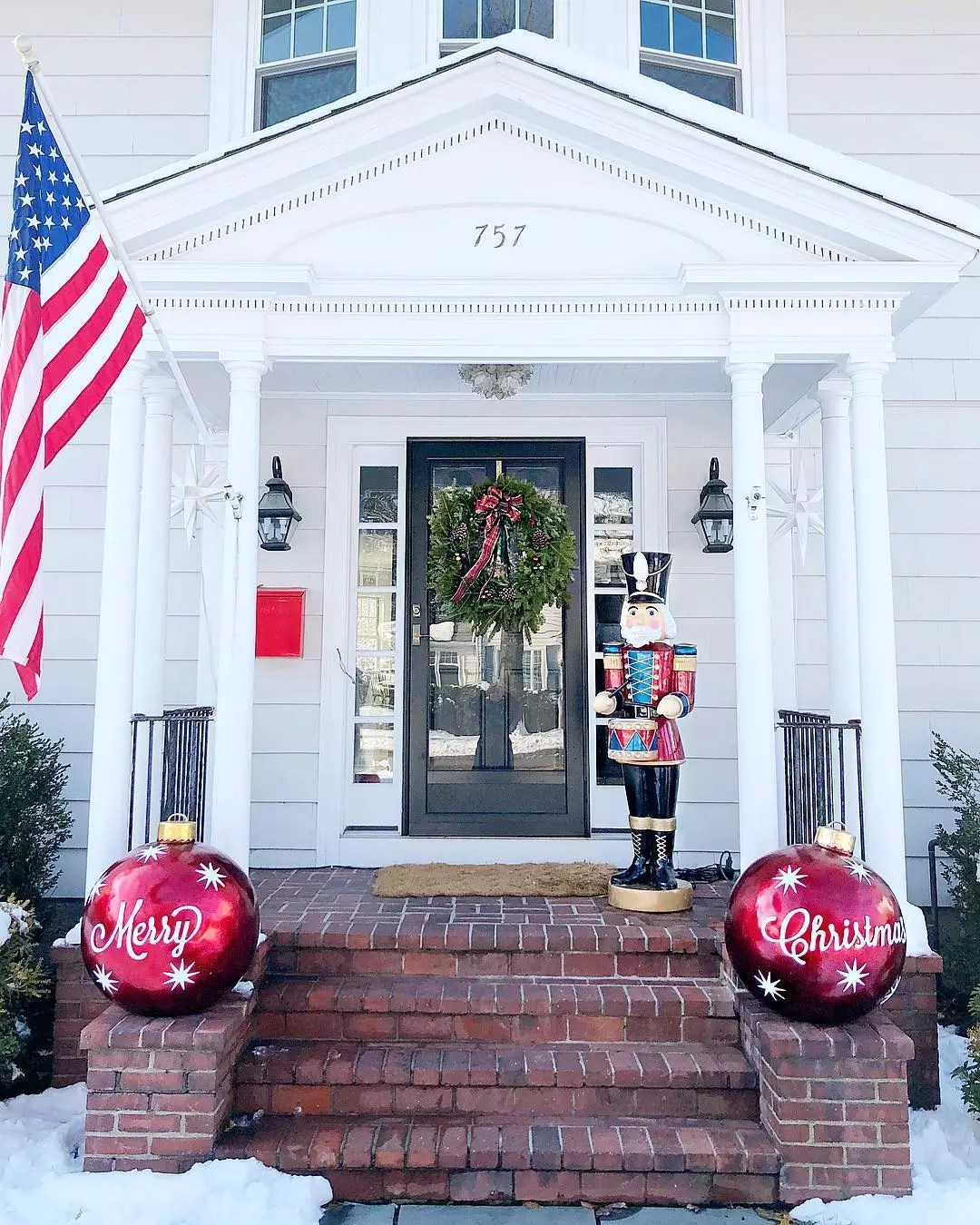 """A front porch features two large DIY red ornaments saying """"Merry Christmas"""" on either side. Photo by Instagram user @honeyandfitz."""