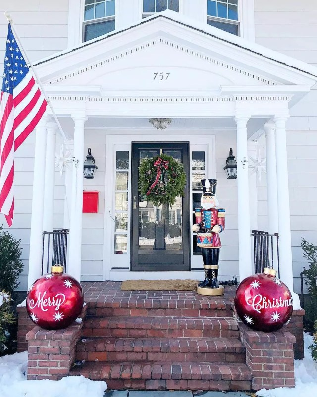 "A front porch features two large DIY red ornaments saying ""Merry Christmas"" on either side. Photo by Instagram user @honeyandfitz."