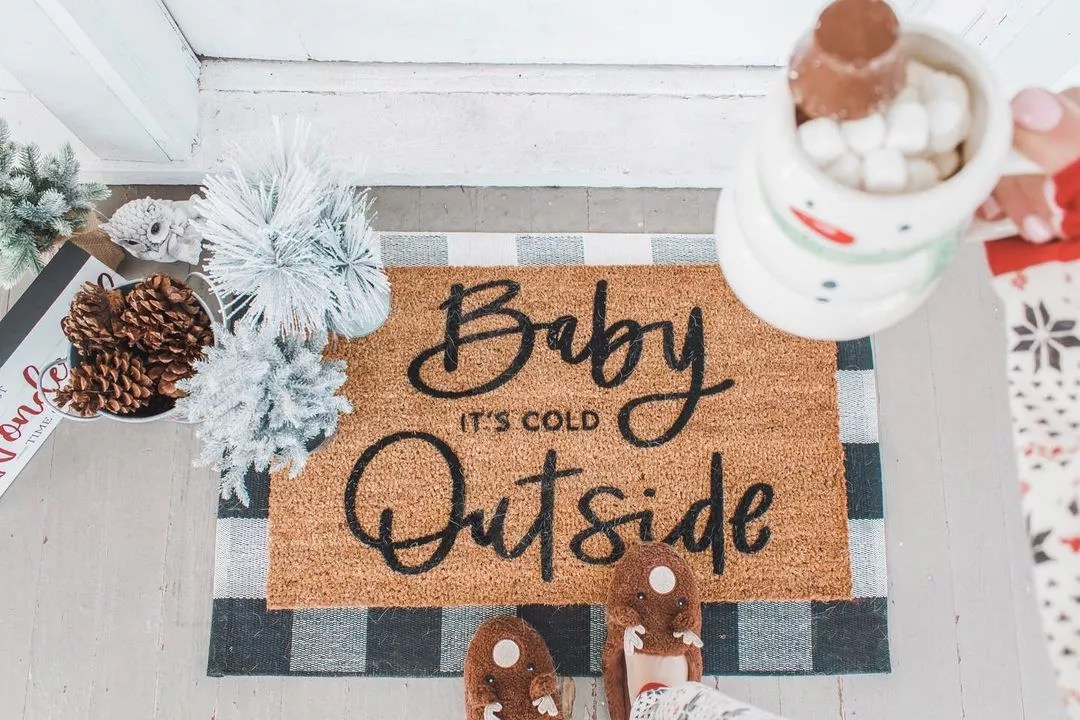 """Coconut welcome mat on the front porch with the song title """"Baby, It's Cold Outside"""" written in cursive. Photo by Instagram user @molly.elizabeth.foster."""