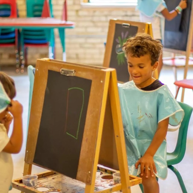 Child painting at an easel at the Grand Rapids Childrens Museum. Photo by Instagram user @grcmuseum
