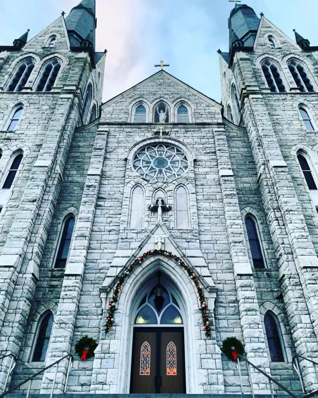 Sacred Heart Parish imposing against the sky, with garland around the entrance doorframe and a wreath on either side of the entry. Photo by Instagram user @travelwithlove.usa.