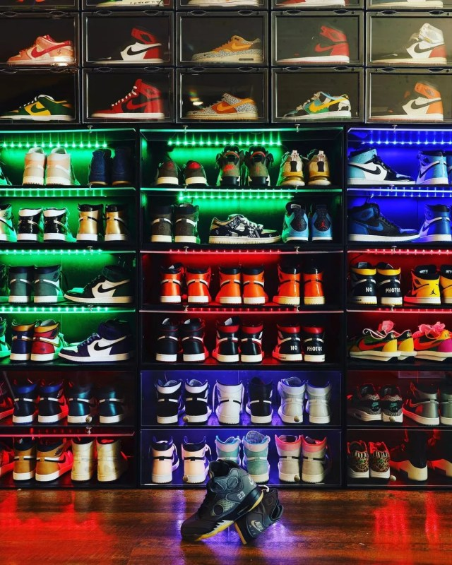 Colorful sneakers organized on shoe racks. Photo by Instagram User @mysneakerthrone