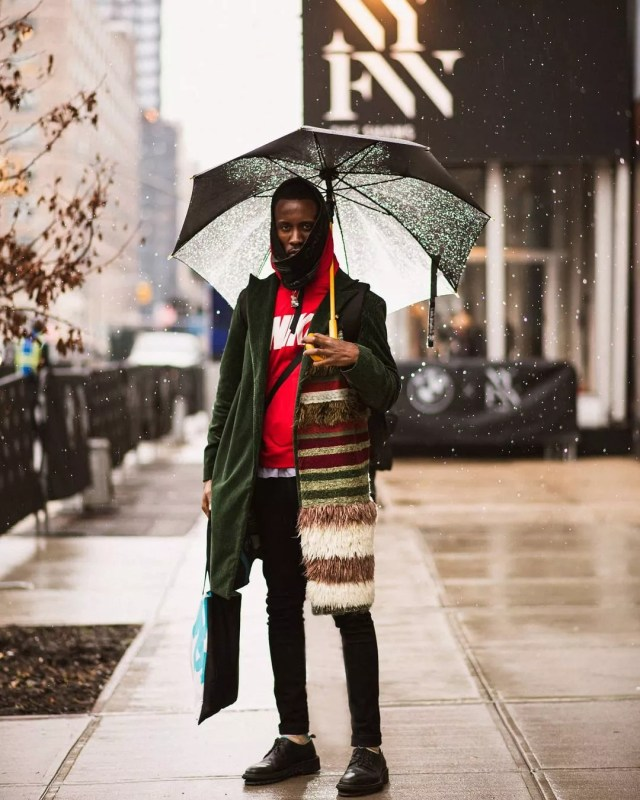 Man Standing Outside of an Event at New York Fashion Week in the Rain. Photo by Instagram user @cswongphoto