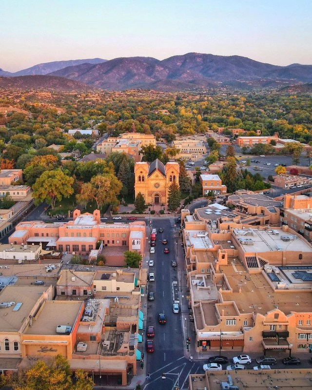 Drone photo of Santa Fe at twilight with mountains in the background. Photo by Instagram user @airscloudsantafe.