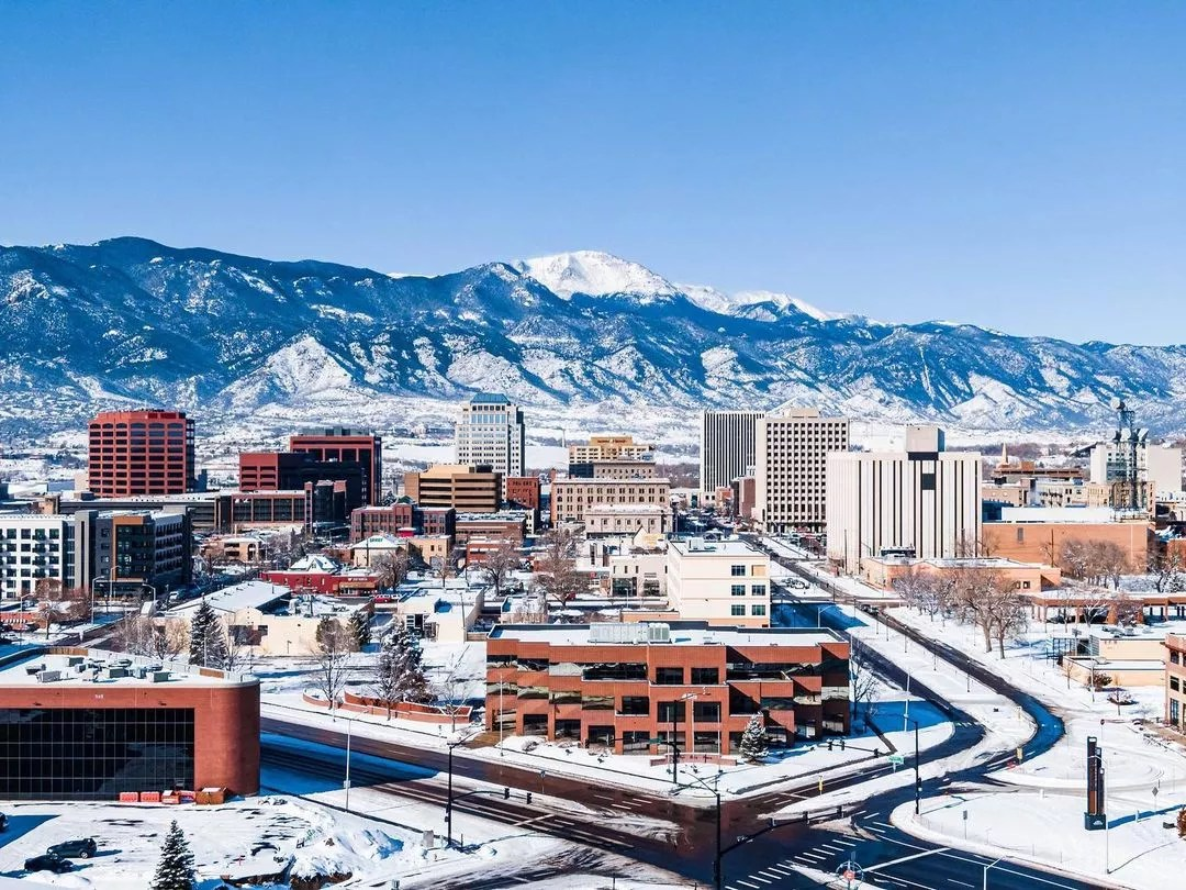 Photo of snowy Downtown Colorado Springs and mountains. Photo by Instagram User @cityofcos