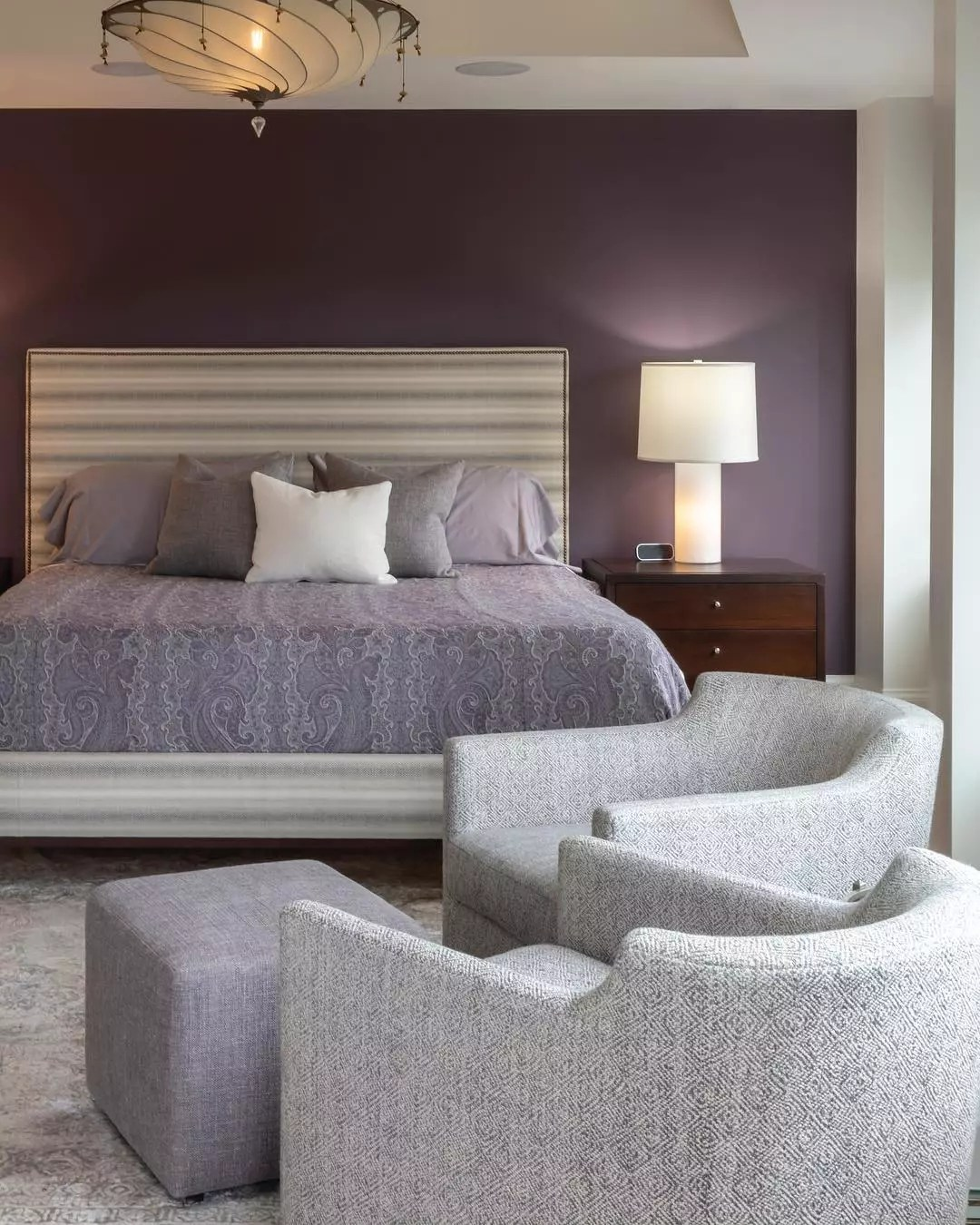 Plum accent wall in a room with a lavender bed and light gray chairs. Photo by Instagram user @katezeidlerdesign.