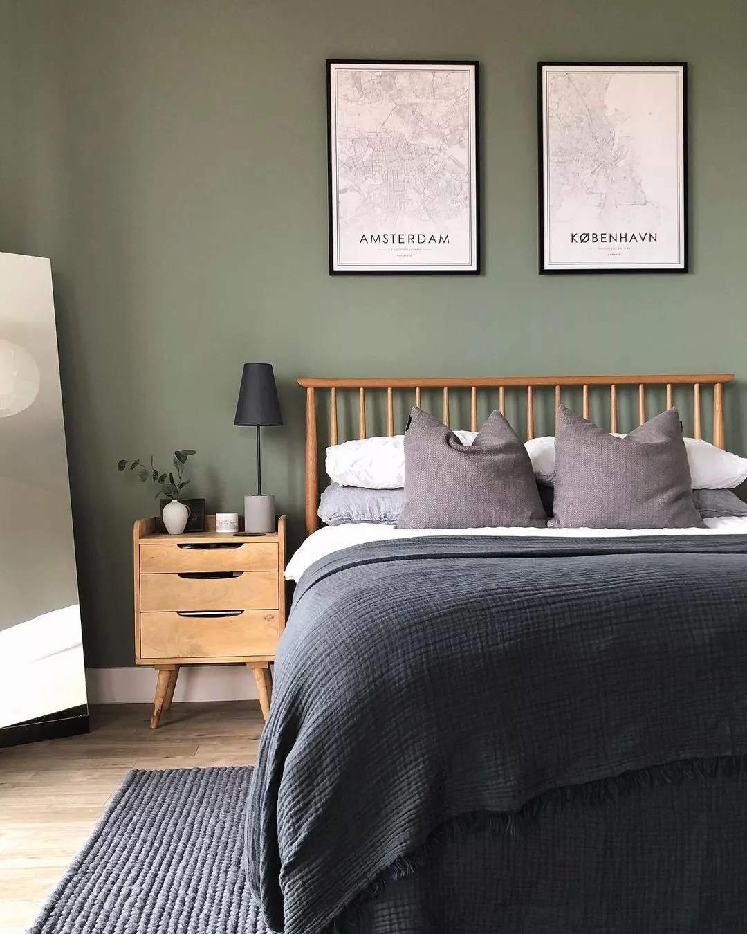 Bed against a sage green wall. Photo by Instagram user @natlimbrey.