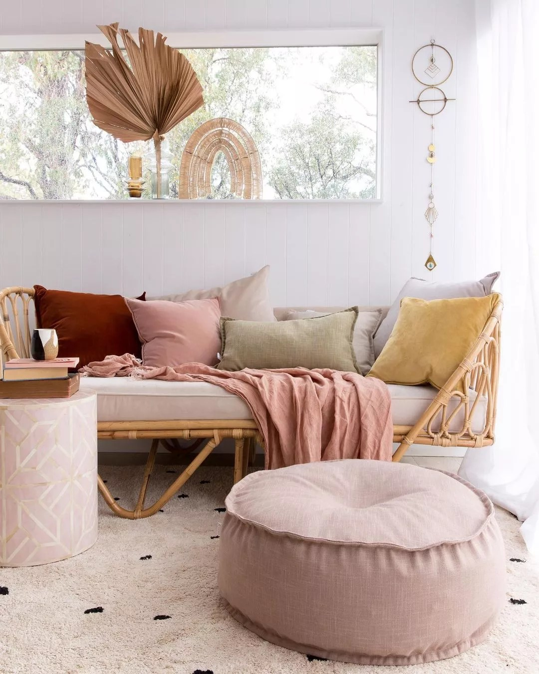 Short daybed in a bamboo frame as a sofa, a light pink pouf across it helps tie the room together as a warm neutral color. Photo by Instagram user @onyxandsmoke.