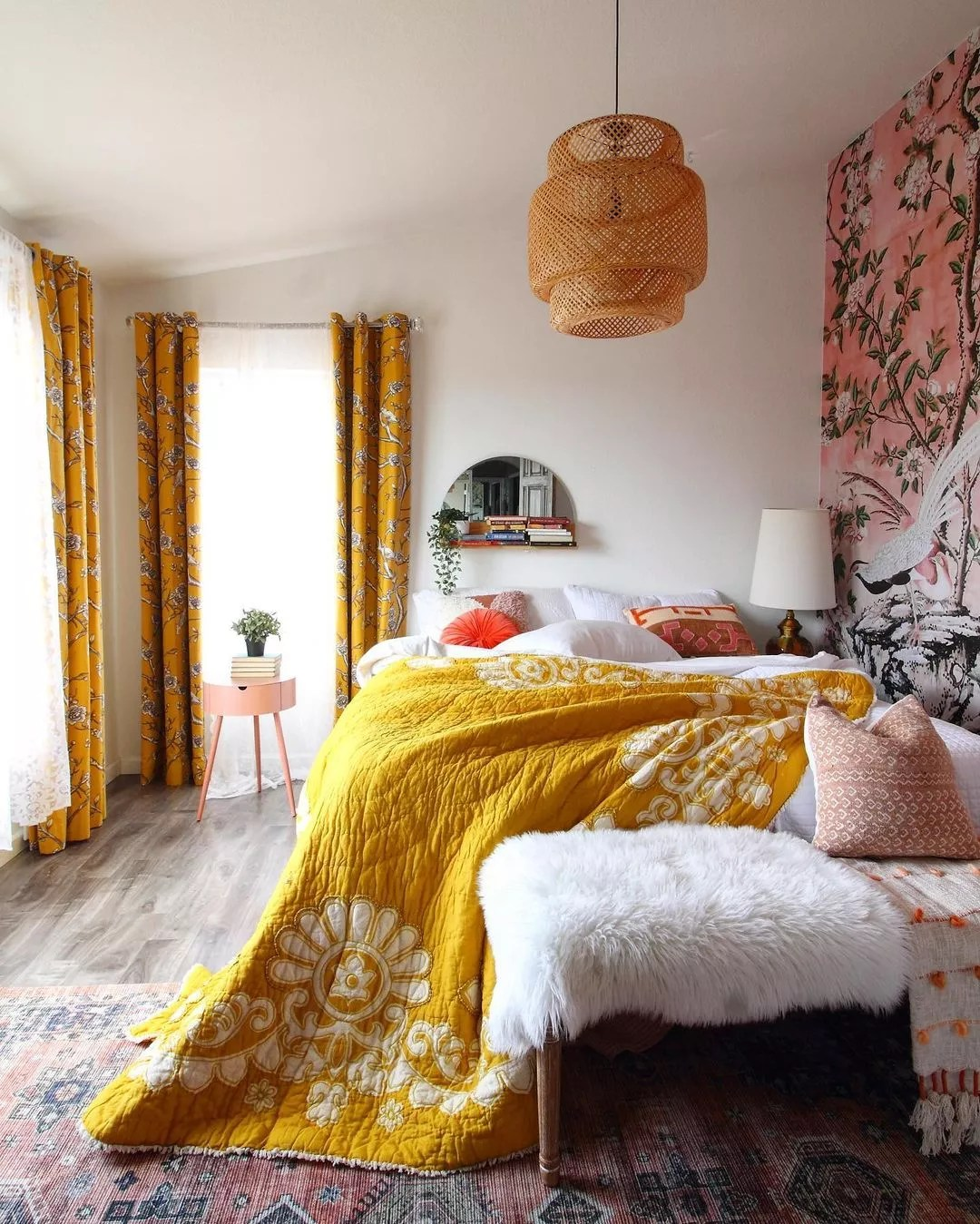 Bedroom with large windows, a lamp to the left of the bed and a hanging light with a wicker shade. The room rug has a faded, antique effect on an aztec design, and an accent wall with a scene of two birds amidst a pink sky and gentle, budding branches of a flowering tree. Photo by Instagram user @raveinteriordesign.