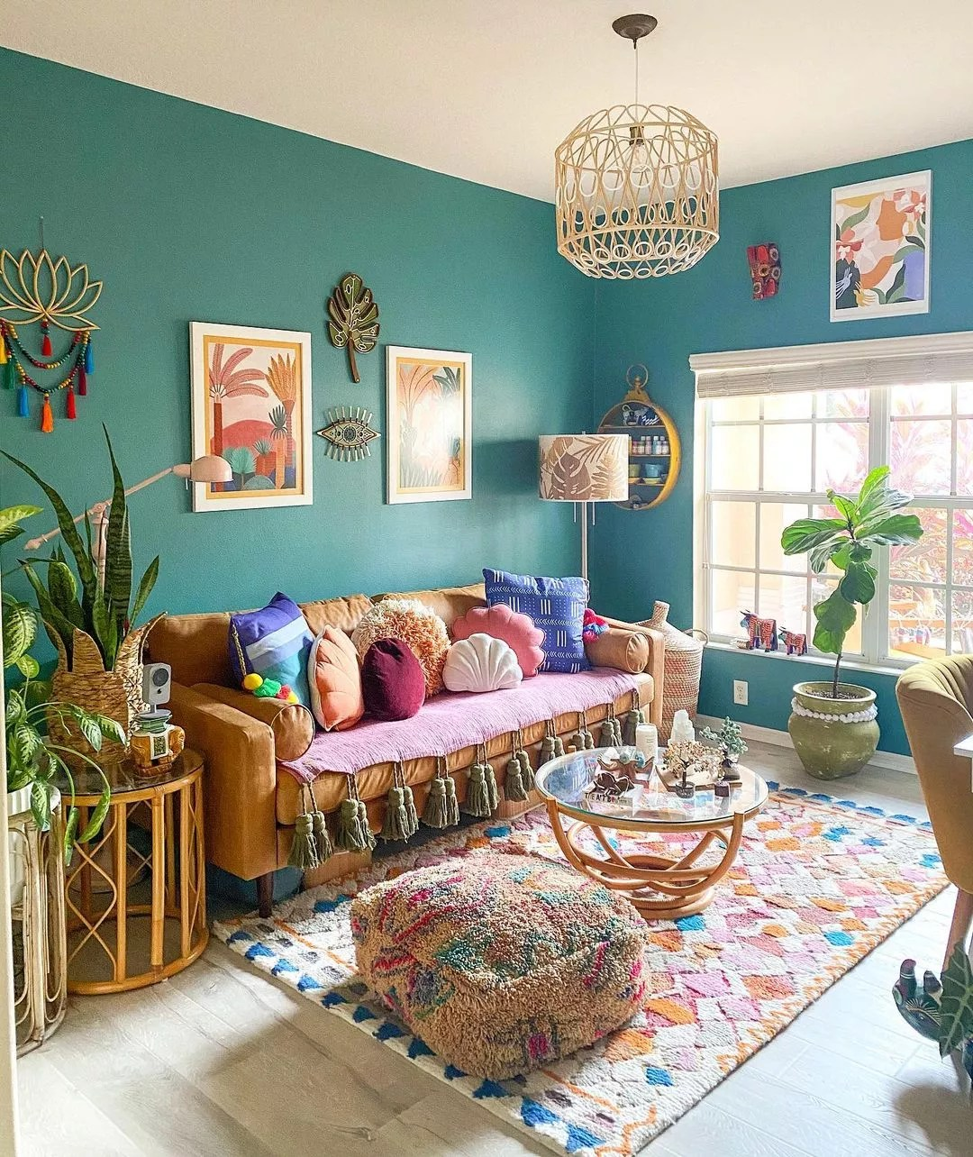 Living room with teal walls and brightly colored pillows, rug, wall art. Photo by Instagram user @mango_manor.