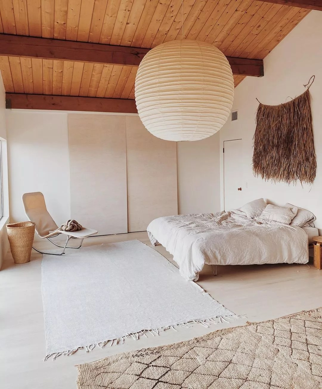 Airy, minimally designed bedroom with large paper lantern style light fixture. Photo by Instagram user @maraserene