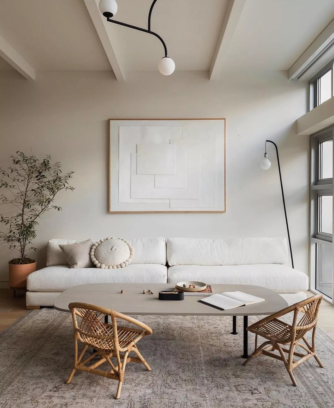 Japandi styled living room with wooden scandi chairs and soft, white sofa. Photo by Instagram user @haris.kenjar