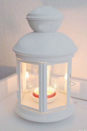 Photo B white hexagonal lantern with candle