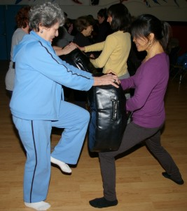 Joyce Murphy (left), Bixia Pan (right) practice self defense moves during the Women's Self Defense Workshop taught by Shifu Billy Greer (photo by Nancy Greer)