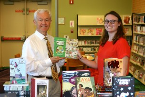 Skip Auld, Library CEO receives graphic novels from Catherine Fraas of the Small Press Expo at the Crofton Community Library.