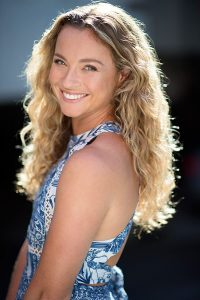 Kylie Loveday wearing a halterneck white and blue dress with her long golden locks falling over her shoulders