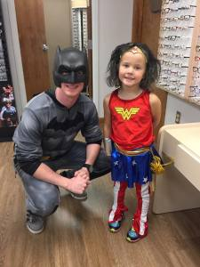 Optometrist dressed as Batman with small child