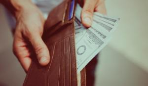 Caucasian hands holding a wallet, with one hand holding hundred dollar bills out of it.