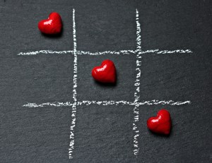 Three hearts in a row in tic tac toe setting. Polyamory