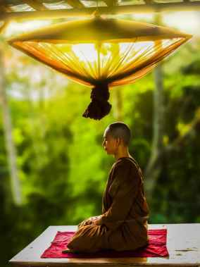 monk meditating underneath a lamp