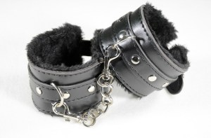 black leather handcuffs with black fur inside.