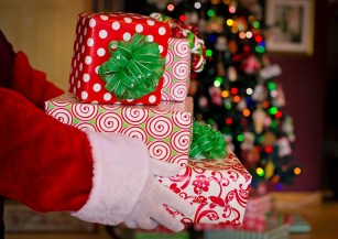 Santa hands holding wrapped gifts