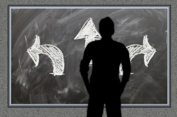 silhouette of a man looking at a blackboard with 3 arrows pointing in different directions