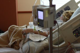 woman sitting in a hospital bed with an IV machine connected