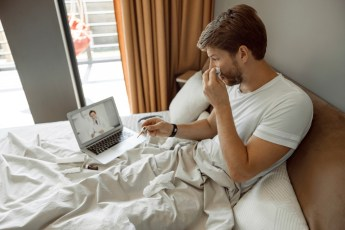 caucasian man in bed with a tissue in one hand and thermomter in the other with a laptop on the bed and a doctor on the screen.