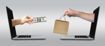 hand out of one laptop screen with money handing it to another hand that is outside a laptop screen with a brown bag.