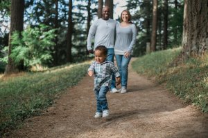 african american man with his arm over a caucasian woman with both watching a little boy running ahead of them.