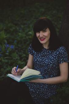 caucasian woman sitting outside writing in a journal while smiling