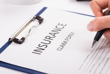 insurance claim form with a caucasian hand holding a pen to it