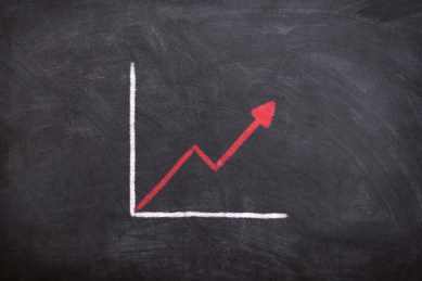 black chalkboard with two white lines forming a line graph, with a red line going upwards in the graph.