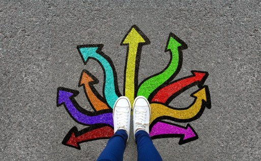 persons legs with white sneakers on in the middle of many different colored arrows around the feet pointing in different directions.