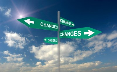 change written on many freen arrow signs pointing in different directions.