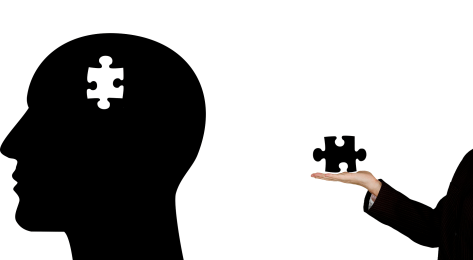 black silhouette of a head with a white puzzle piece and a persons hand holding the black missing puzzle piece.