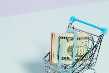 shopping cart with money held in a paperclip inside of it.