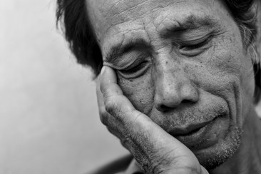older asian man with his eyes closed and his palm on his cheek