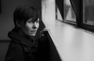 black and white picture of a caucasian woman looking out a window