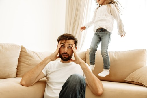 caucasian man sitting on the floor with both hands holding his head and a young girl jumping on the couch behind him.