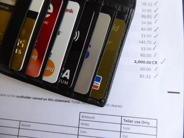 credit cards in a wallet next to a statement