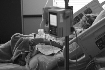 black and white picture of a woman sitting in a hospital bed with an IV in her