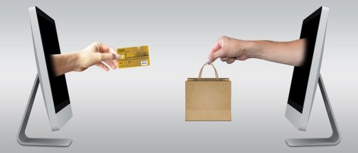 hand with credit card coming out of a laptop to another hand across with a bag coming out of a screen