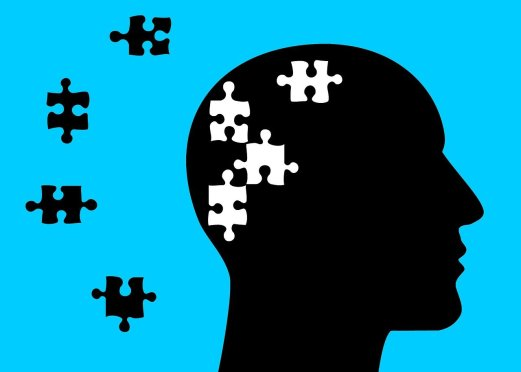 black silhouette of a head with white puzzle pieces in it and the black puzzle pieces next to the silhouette