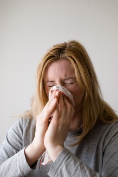 caucasian woman blowing her nose into a tissue