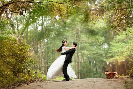 asian woman and man in wedding outfits hugging in the forest.