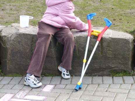 child sitting on a stone row with crutches leaning on the stone row next to child.