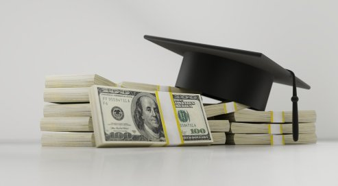 black graduation cap laying on top of stacks of money